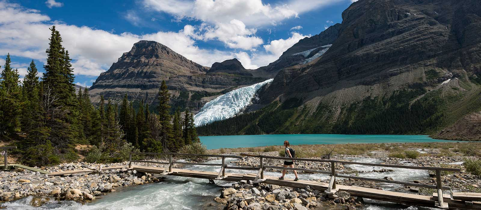 Hiker crossing wooden bridge over river beside turquoise lake, mountain glacier in background