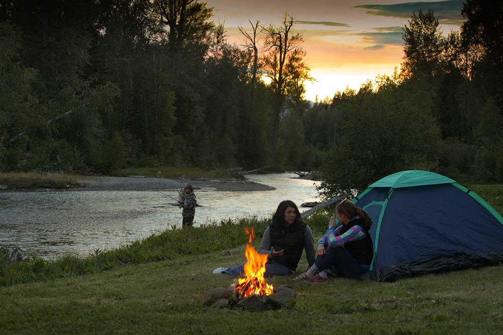 Camp fire by the river, tenting