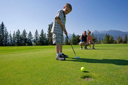 Kid playing golf, putting
