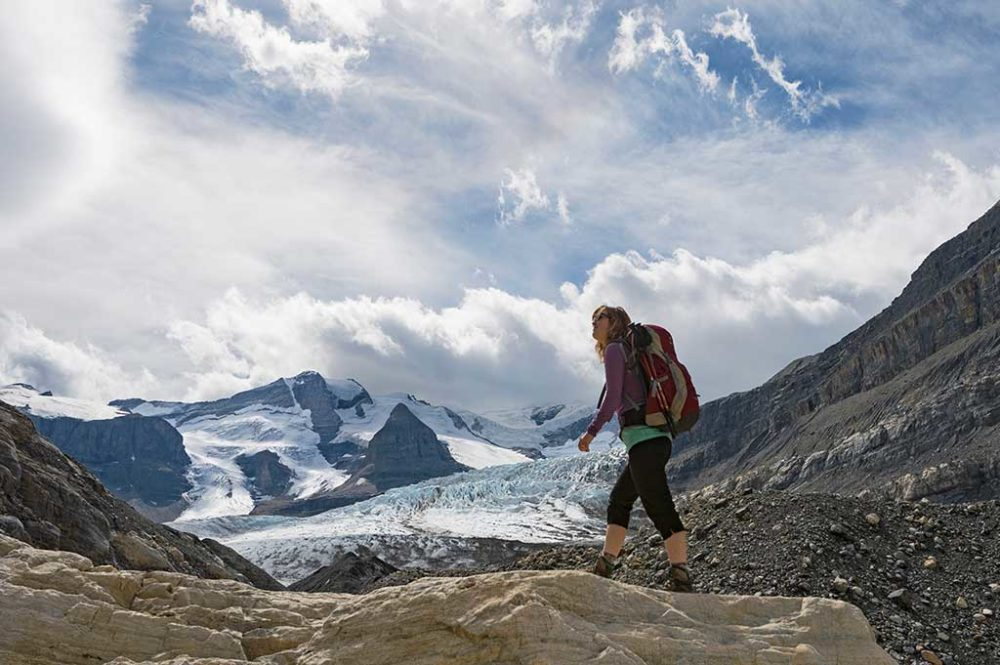 Woman hiking on mountain trail with glacier and mountain peak ahead