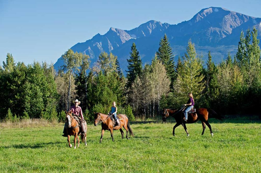 Riding horses through the valley with mountain scenery