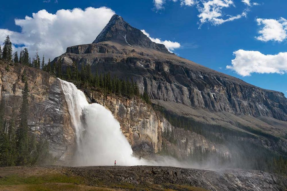 Enormous waterfall gushing over a rock face on Mt Robson with hiker in front
