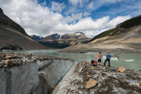 Glacial run-off from Mount Robson, 2 hikers viewing edge of lake