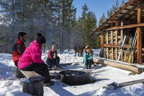 Group of nordic skiiers sitting around a campfire, roasting marshmallows, beside a trail cabin