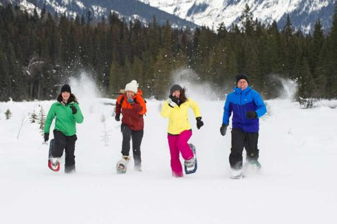 Four people in bright ski clothes racing each other on snowshoes, laughing