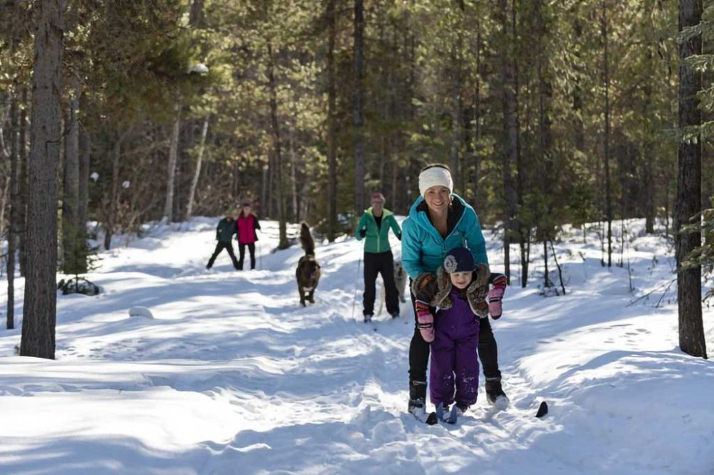 Mother helping child balance on nordic skis on trail in the forest