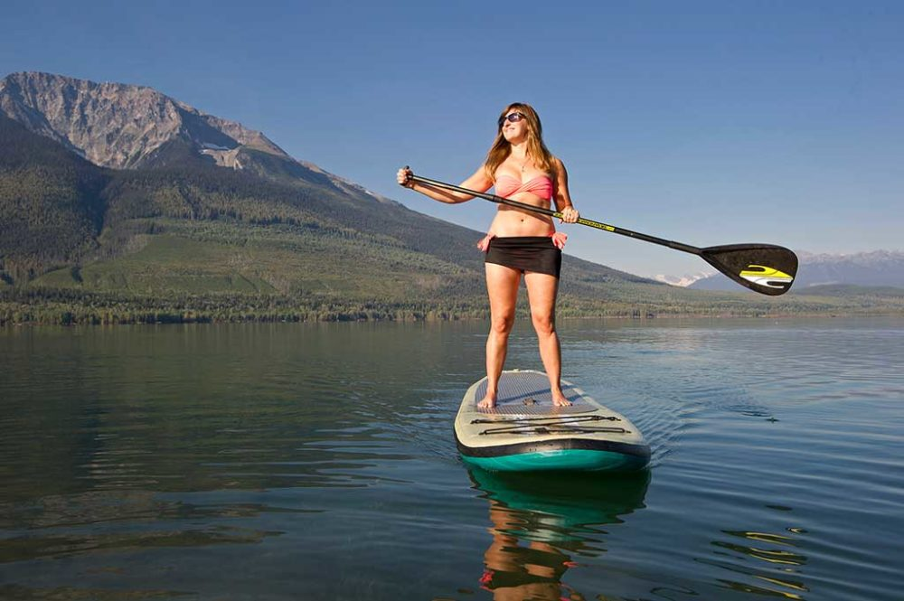 Woman on stand up paddleboard on calm lake