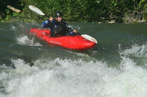 Expert kayaker on white water, paddling fast in red kayak