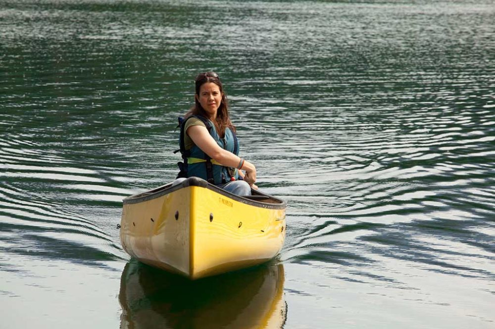 Woman calmly steering yellow canoe on lake