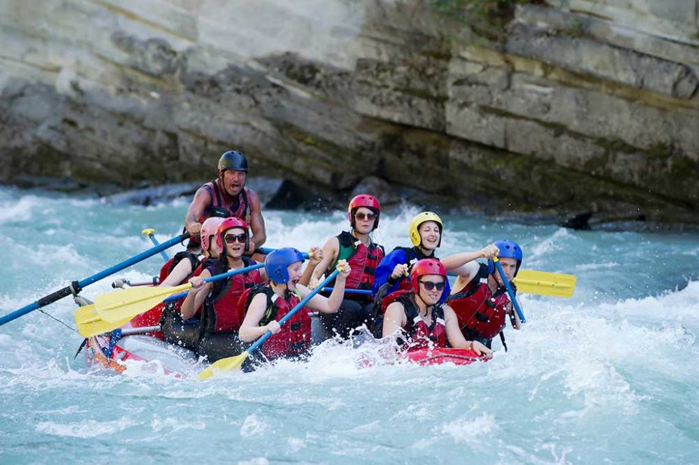 The thrill of white water rafting - group on river having fun