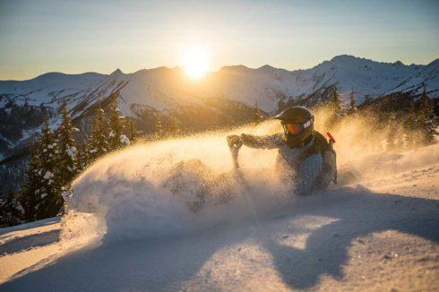 Setting sun backlighting snowmobiler carving through deep powder