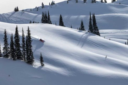 Rolling hills covered in deep snow, snowmobile carving fresh tracks