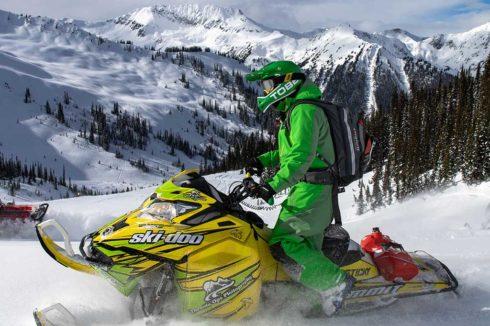 Snowmobiler on ski-doo with mountain vista behind