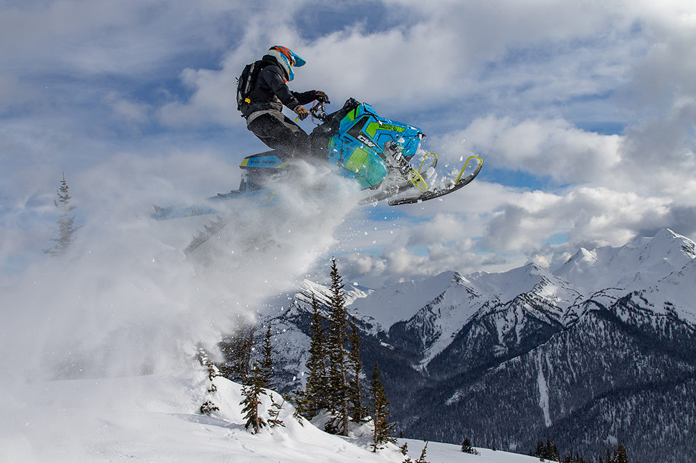 Snowmobiler soaring off the top of a steep slope, powder flying
